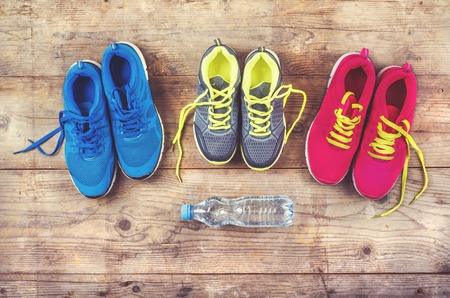 Various pairs of colorful sneakers laid on the wooden floor background photo