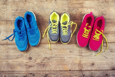 Various pairs of colorful sneakers laid on the wooden floor background 版權商用圖片 - 36096506