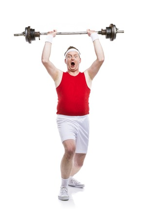 tries: Funny weak body builder tries to lift a weight. Studio shot on white background.