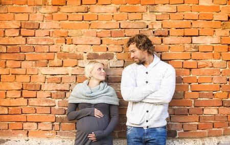 embarazada: Pareja embarazada joven feliz que se coloca fuera de una vieja casa de ladrillo.