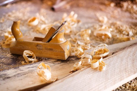 Wood planer, wooden planks and shavings at carpenters workshop Stock Photo