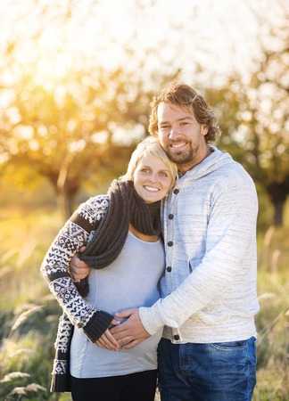 woman sweater: Happy young pregnant couple spending time together outside in green nature.