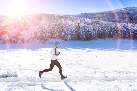 ropa de invierno: Trotar deportista joven afuera en el soleado parque de invierno