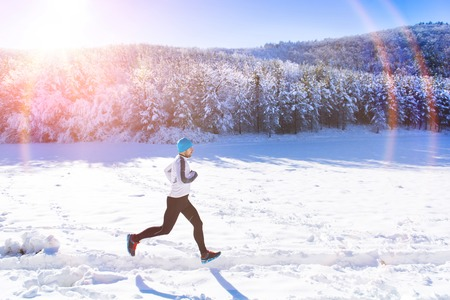 one young man: Young sportsman jogging outside in sunny winter park