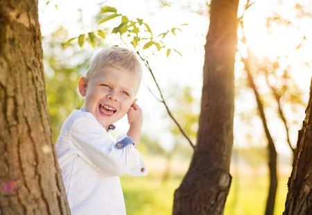 boyhood: Little boy playing and climbing a tree outside in a park