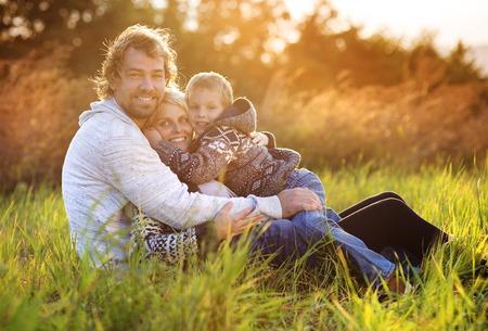 abrazar familia: Feliz familia joven pasar tiempo juntos fuera en la naturaleza verde tiempo.