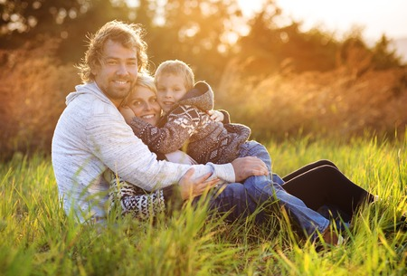 parent child: Happy young family spending time together outside in green nature. Stock Photo