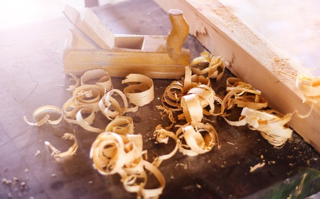 wood shavings: Wood planer, wooden planks and shavings at carpenters workshop Stock Photo