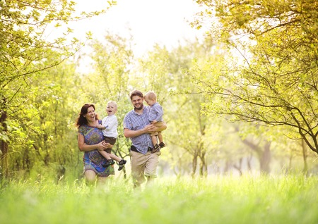 happy family: Feliz familia joven pasar tiempo juntos fuera en la naturaleza verde tiempo.