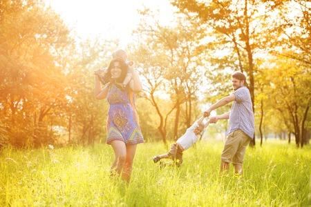 familias jovenes: Feliz familia joven pasar tiempo juntos fuera en la naturaleza verde tiempo.