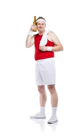 hombre tomando cerveza: Divertido débil constructor cuerpo trata de hacer ejercicio. Estudio tirado en el fondo blanco.