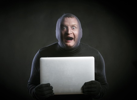 cyber terrorism: Thief in action with balaclava on his face, dressed in black. Studio shot on black background.
