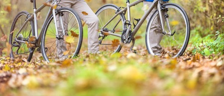 active couple: Unrecognizable active seniors having walk with bike in autumn nature. They having romantic time outdoor. Stock Photo