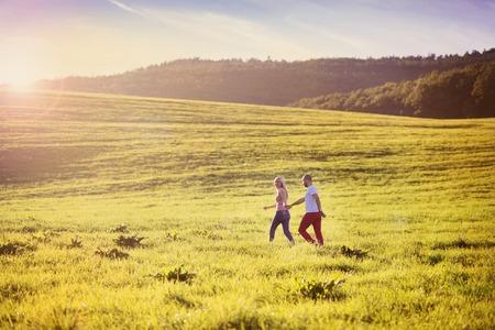 personas abrazadas: Feliz pareja de j�venes que se divierten fuera en un prado Foto de archivo