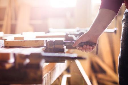 木製の板を一緒に結合する接着剤のクランプをねじ込む大工の手