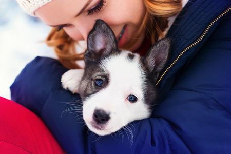 mujer con perro: Mujer joven atractiva que se divierten fuera en la nieve con su perrito perro