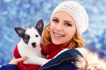 Attractive young woman having fun outside in snow with her dog puppy photo