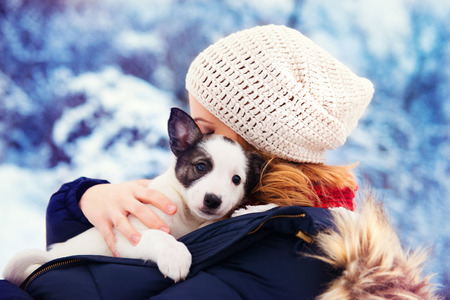 snuggle: Attractive young woman having fun outside in snow with her dog puppy Stock Photo