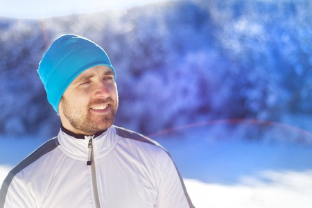 white winter: Young runner warms him up while resting during his training outside in sunny winter park Stock Photo