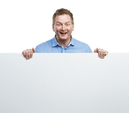 holding blank sign: Young man making funny face, holding a blank sign board. Studio shot on white background.