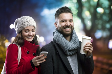 calling on phone: Trendy young hipster couple enjoying nightlife in the city Stock Photo