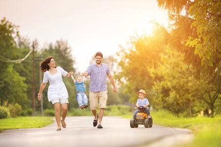 Gelukkig jong gezin plezier buiten op de straat van een dorp Stockfoto - 36597627