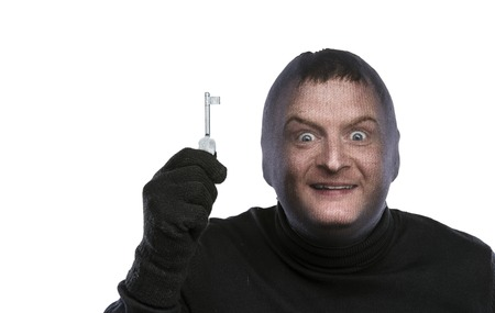 keys isolated: Thief in balaclava making funny faces, dressed in black. Studio shot on white background.