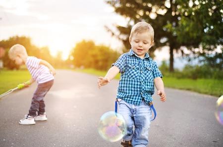 brothers playing: Los ni�os peque�os lindos que juegan y se divierten al aire libre en una calle