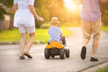 Dzieci: Szczęśliwa młoda rodzina zabawy na zewnątrz, na ulicy wsi