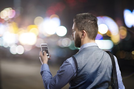 night shirt: Handsome young hipster with his smartphone outside in the night city