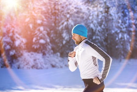 white man: Young sportsman jogging outside in sunny winter park