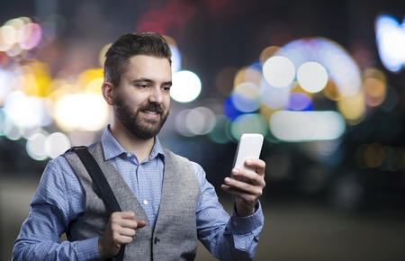 ejecutivos: Inconformista joven hermoso con su tel�fono inteligente fuera de la ciudad la noche