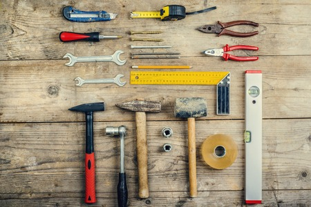 Desk of a carperner with different tools. Studio shot on a wooden background. photo