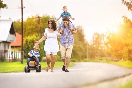 家庭: 快樂年輕的有樂趣的家庭之外的一個村莊的街道 版權商用圖片