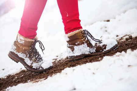 woman hiking: Unrecognizable woman in red trousers and leather boots outside in snow.