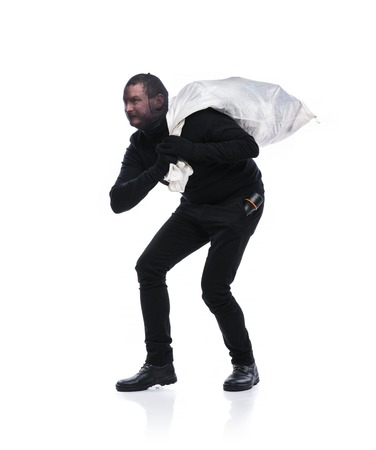 Thief in action carrying a big bag with balaclava on his face, dressed in black. Studio shot on white background. photo