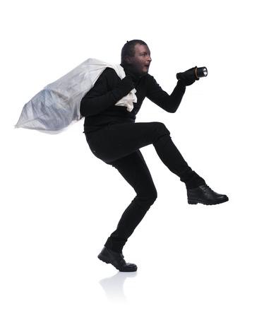 ladrón: Ladr�n en la acci�n que lleva una gran bolsa con pasamonta�as en su rostro, vestida de negro. Estudio tirado en el fondo blanco.
