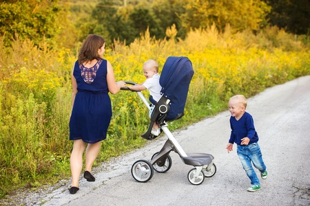 sunglight: Mother and sons on a walk in nature enjoying life together. Stock Photo