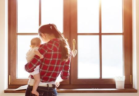 felicidade: Mãe carregando seu bebé pequeno em seus braços.