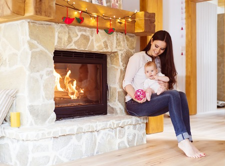 stone fireplace: Mother carrying her little baby girl in her arms.