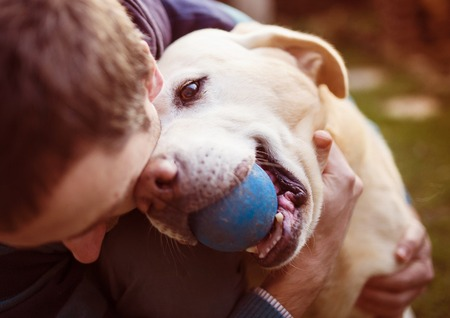 friends hugging: Man having fun and playing with his dog