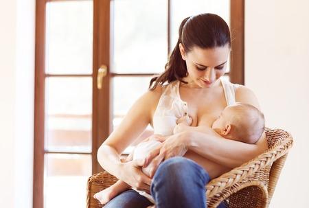 lactancia materna: Madre que amamanta a su pequeño bebé en sus brazos. Foto de archivo