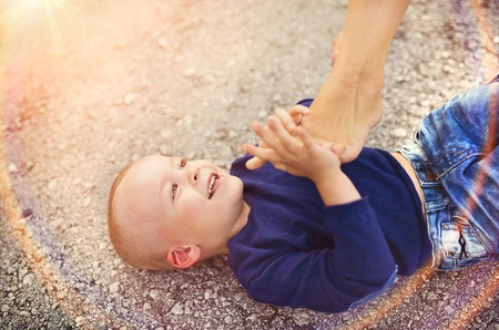 blue jeans kids: Little boy lying on the ground playing with this mother