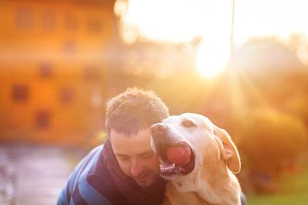 amigos abrazandose: Sirva divertirse y jugar con su perro