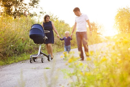 sunglight: Happy family on a walk in nature enjoying life together.