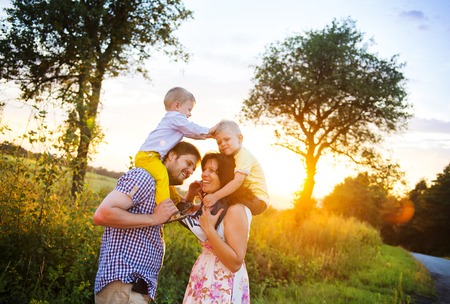 family on grass: Happy young family spending time together outside in green nature. Stock Photo
