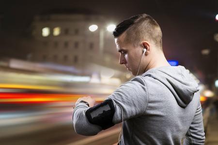 la escucha activa: Trotar Deportista joven en la ciudad de noche