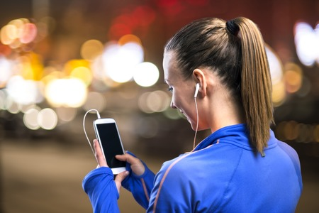 Young woman jogging at night in the city while listening music photo