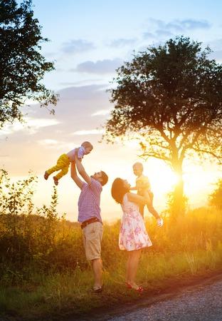 familias unidas: Feliz familia joven pasar tiempo juntos fuera en la naturaleza verde tiempo.