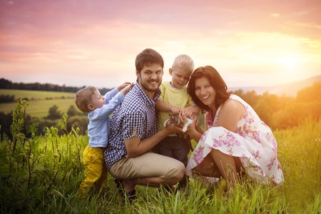 animal park: Happy young family spending time together outside in green nature. Stock Photo